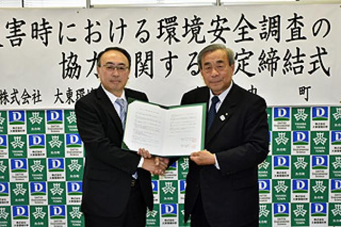 協定書を掲げる高橋昌造町長(右)と小山克也社長