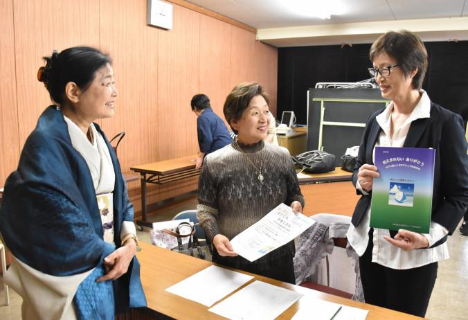 活動報告集を手に、こそだてシップのスタッフらと子育て支援の継続を誓う伊藤怜子理事長(右)