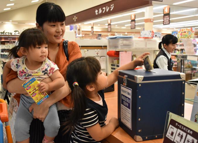 マイヤ大船渡インター店に設置された募金箱に寄付する買い物客の親子=10日、大船渡市立根町