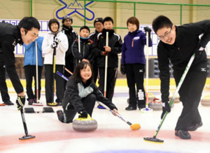 苫米地美智子さん(右から2人目)らの指導を受けながらカーリングを楽しむ子どもたち。世代を超えて競技に親しんでいる
