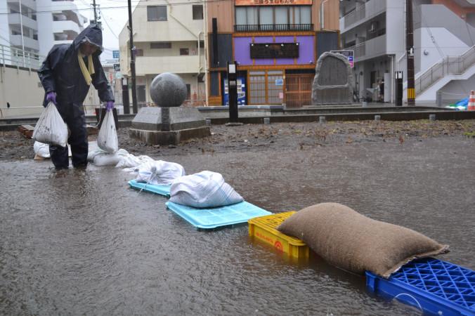 土のうやビールケースを積み「橋」を作るホテル従業員=9日午前9時7分、釜石市大町
