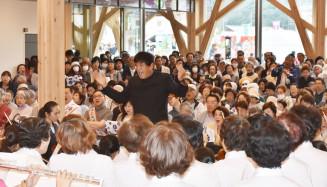 オープニングコンサートで佐渡裕さん(中央)の指揮に合わせて歌い開館を祝う来場者