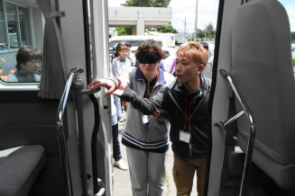 視覚障害者役と同行者役でバスの乗降を体験する参加者