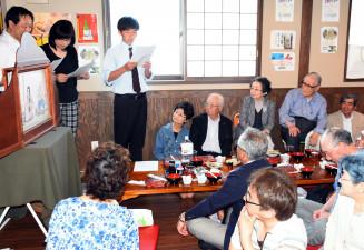 金野静一さん(右奥から2人目)の前で紙芝居を披露する「なるせすわんず」の会員ら