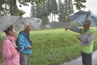 骨寺村荘園遺跡で観光客をガイドする斉藤三郎会長(右)。拡張登録の長期化が懸念される中、地道な活動を継続する=一関市厳美町