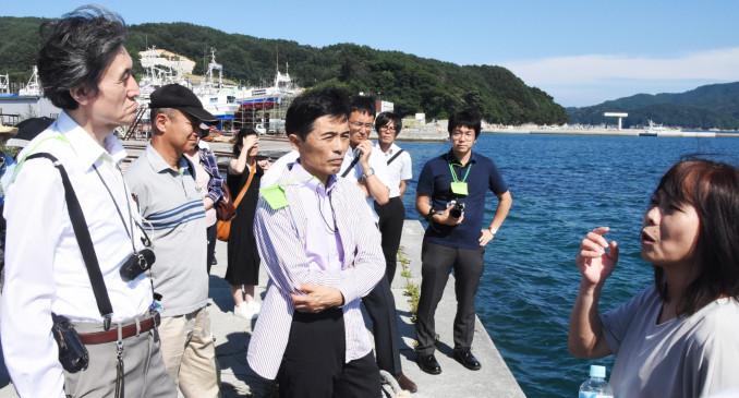 地元の語り部ガイドから大槌町の被災状況を聞き、震災の教訓を胸に刻む参加者=27日、大槌町赤浜