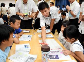多田俊輔教諭(中央)の指導の下、複数の新聞記事から共通点を考える大槌学園の6年生