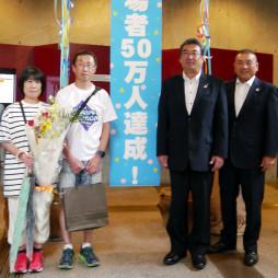 50万人目の入場者となり記念撮影する中川並樹さん(左から2人目)、規子さん夫妻