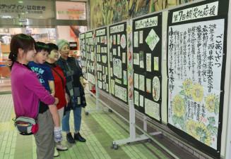 西日本豪雨の被災者に励ましの思いを込めた絵手紙展示会を観賞する駅利用者ら