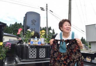 墓前で毅さんから贈られたかっぽう着を手にする松本そめ子さん。「仏様の前では涙は見せたくない」と前を向く=宮古市田老