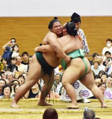 声援を受けながら、必死に相手を引きつける錦木(左)