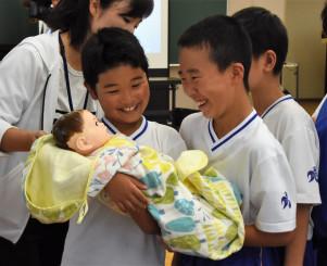 赤ちゃんの人形を抱っこして重さを確かめる児童
