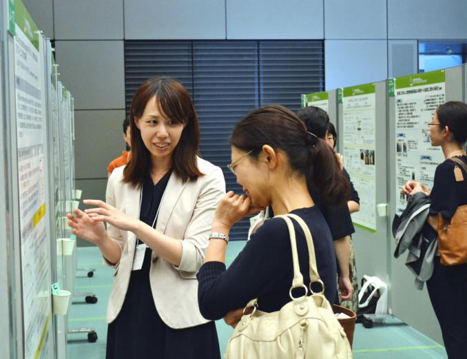 ポスターセッションで互いの研究を紹介する女性研究者ら