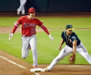 アスレチックス戦の7回、遊撃への内野安打を放ち、一塁を駆け抜けるエンゼルス・大谷翔平。一塁手オルソン=オークランド(特派員・小田野純一撮影)