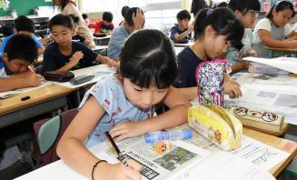 記事をスクラップブックに貼り、要約と感想を書き込む5年2組の児童