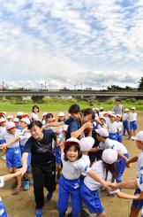 教育実習生と一緒に手をつなぎ、笑顔で遊ぶ仁王小の児童=21日、盛岡市大沢川原・北上川公園