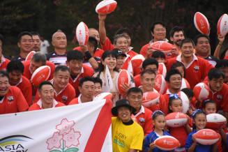 試合前に行われた記念写真の撮影に笑顔を見せる新日鉄釜石OBら