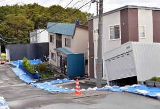 地震による液状化で建物が傾き、路面がゆがんだ住宅街=26日、札幌市清田区(報道部・石森明洋撮影)