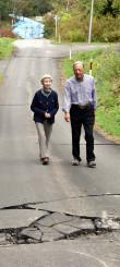 地震の爪痕が残る自宅周辺を歩く大戸洋儀さん、伸子さん夫妻。道路には亀裂が残り、崩れた斜面にはブルーシートがかけられている=27日、北海道厚真町豊沢