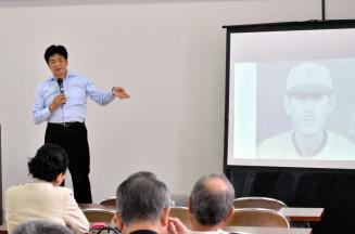 久慈次郎について写真を見せながら語る黒田伸さん