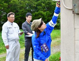 北海道内や新潟県からの派遣職員とチームを組み、家屋の傾きなどを調べる岩泉町の長崎綾乃さん(右)=28日、北海道安平町追分