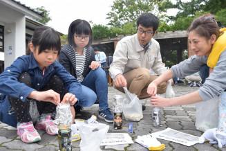 アルミ缶と牛乳パックを使った野外炊飯に挑戦する参加者