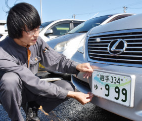 図柄入りナンバープレートを取り付ける神山正行さん