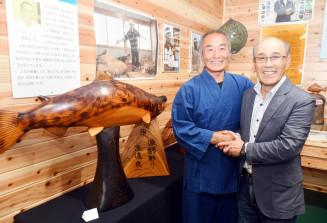 自作の木彫り作品を大西義孝さん(右)に手渡した深渡栄一さん