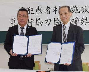 災害時の避難に関する協定書を手にする斉藤純理事長(右)と山下欽也社長