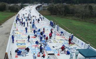 復興を願って閉伊川横断橋の床板にメッセージを書く花輪中の生徒=10日、宮古市田鎖(本社小型無人機で撮影)