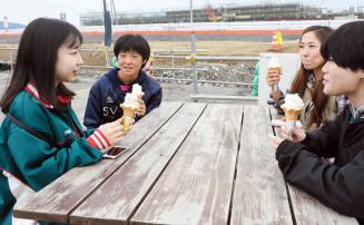 奇跡の一本松を見学後、地元のソフトクリームを食べながら受け入れ家庭の吉田愛さん(右奥)と懇談する新栄高の生徒