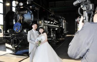 思い出のSL銀河の前で写真撮影に臨む柳渡祐太さん、加奈絵さん夫妻