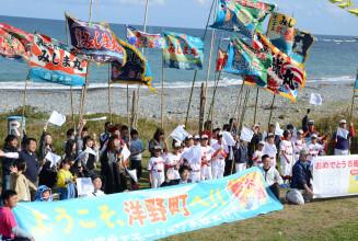 大漁旗や横断幕で乗客に感謝を伝える参加者=洋野町種市、宿戸大浜