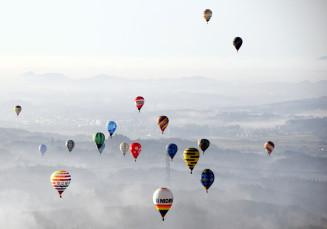 体験搭乗した熱気球から撮影した一関市内。朝もやに包まれる中、色とりどりの競技用気球が彩りを添えた