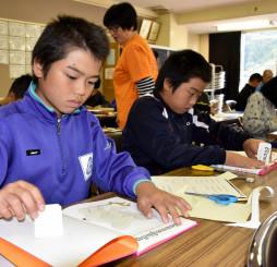 日本語の絵本に現地語訳のシールを貼る児童