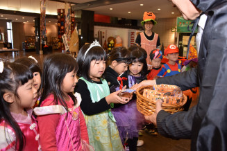 阿部大司社長から菓子を受け取る子どもたち