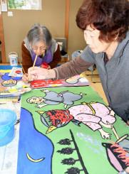 紙芝居の色塗りを進める若葉会のメンバー
