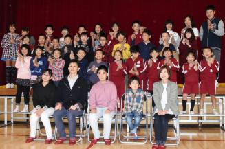 遠藤快莉さん(前列中央)一家から届けられたサツマイモを手に笑顔を見せる白山小の児童