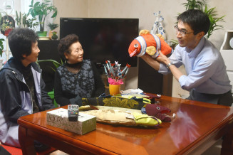 浜のかあちゃんサークルから手作りの人形を受け取った平山巌雄さん(右)