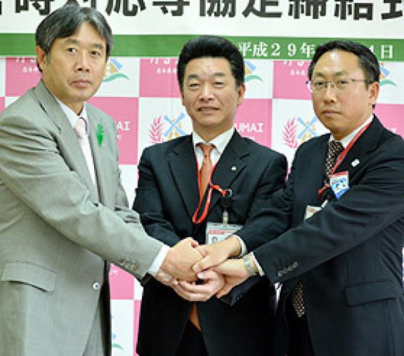 協定を結び、握手する(左から)山本賢一町長、木戸口春彦局長、壬生政美局長