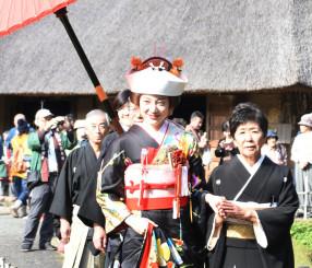 花嫁道中でかやぶきの古民家の並ぶみちのく民俗村内を練り歩く平野千秋さん(中央)