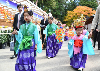 紅葉が色づく境内を練り歩く子どもたち