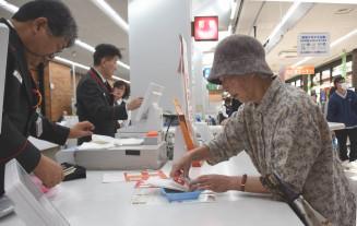 年賀はがきを買い求める市民(右)