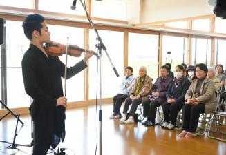 災害公営住宅の住民に新曲を披露する式町水晶さん(左)