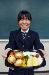 地元産の食材を活用した「いわてまち弁当」を掲げる橘実保さん。道の駅石神の丘の産直施設で限定販売される
