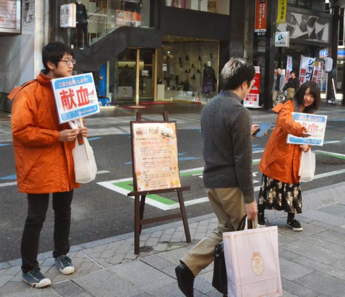 チラシ入りのポケットティッシュを配り、献血への協力を呼び掛ける三浦綾華さん(右)と久慈涼太さん