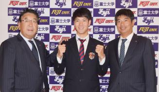 長島哲郎スカウト部長(左)らの訪問を受け、笑顔でガッツポースする富士大の鈴木翔天=花巻市・富士大