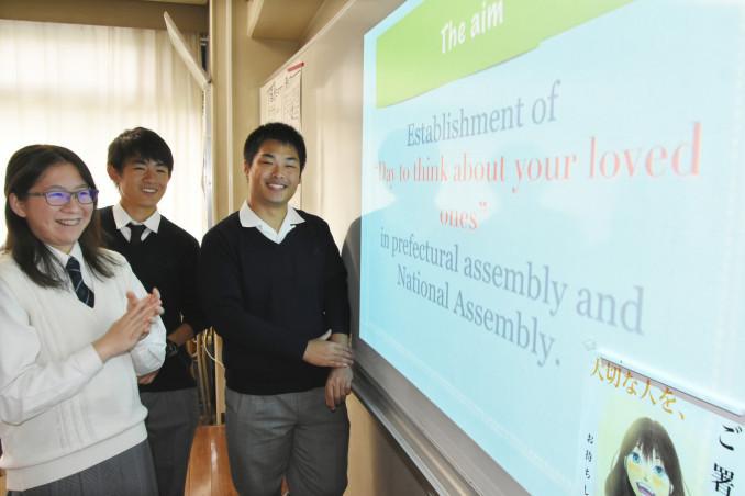 文化祭で「大切な人を想う日」の英語版動画を流し、署名を呼び掛ける(左から)片岡真優さん、小田切颯人さん、西島史さん