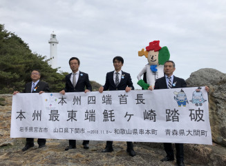 魹ケ崎で灯台を背に記念写真に納まる(左から)山本正徳市長、前田晋太郎市長、田嶋勝正町長、金沢満春町長