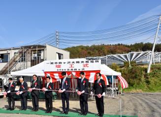 テープカットで鈴ケ沢太陽光発電所の完成を祝う関係者